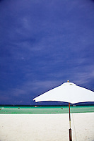 White beach umbrella starkly contrasts against the clear turquoise tropical waters and deep blue skies on Boracay, Philippines.