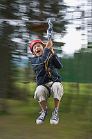Boy (7-9) riding zip-line in forest