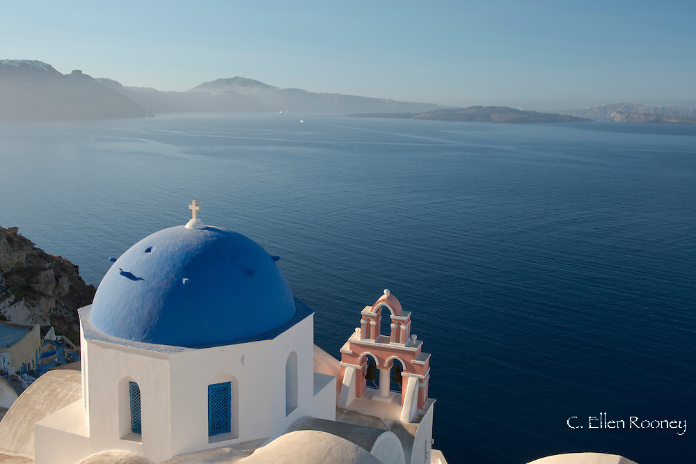 A blue domed church and pink bell tower overlooking the caldera in Oia, Santorini, The Cyclades, The Aegean, The Greek Islands, Greece, Europe