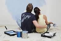 Couple looking up at half-painted wall