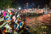 28 NOVEMBER 2012 - BANGKOK, THAILAND: People launch their krathongs in the Chao Phraya River on Loy Krathong at Wat Yannawa in Bangkok. Loy Krathong takes place on the evening of the full moon of the 12th month in the traditional Thai lunar calendar. In the western calendar this usually falls in November. Loy means 'to float', while krathong refers to the usually lotus-shaped container which floats on the water. Traditional krathongs are made of the layers of the trunk of a banana tree or a spider lily plant. Now, many people use krathongs of baked bread which disintegrate in the water and feed the fish. A krathong is decorated with elaborately folded banana leaves, incense sticks, and a candle. A small coin is sometimes included as an offering to the river spirits. On the night of the full moon, Thais launch their krathong on a river, canal or a pond, making a wish as they do so.    PHOTO BY JACK KURTZ