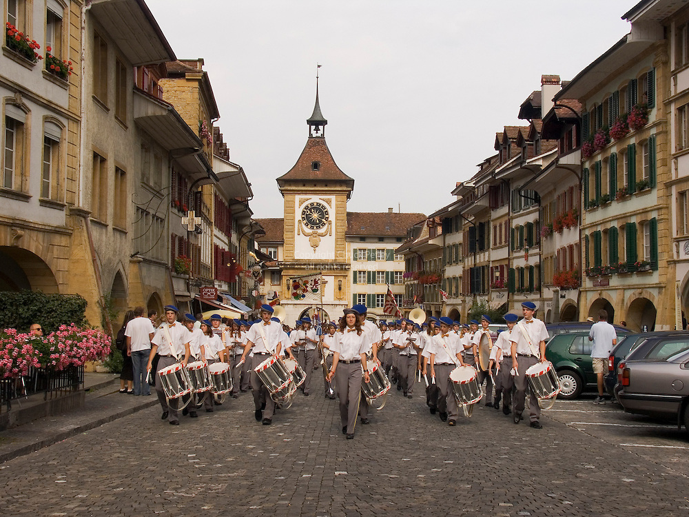 Kadetten Murten marching band in parade at end of weekend music and sports competition for youth, Hauptgasse and historic medieval city gate and clock, Murten, Switzerland<br />