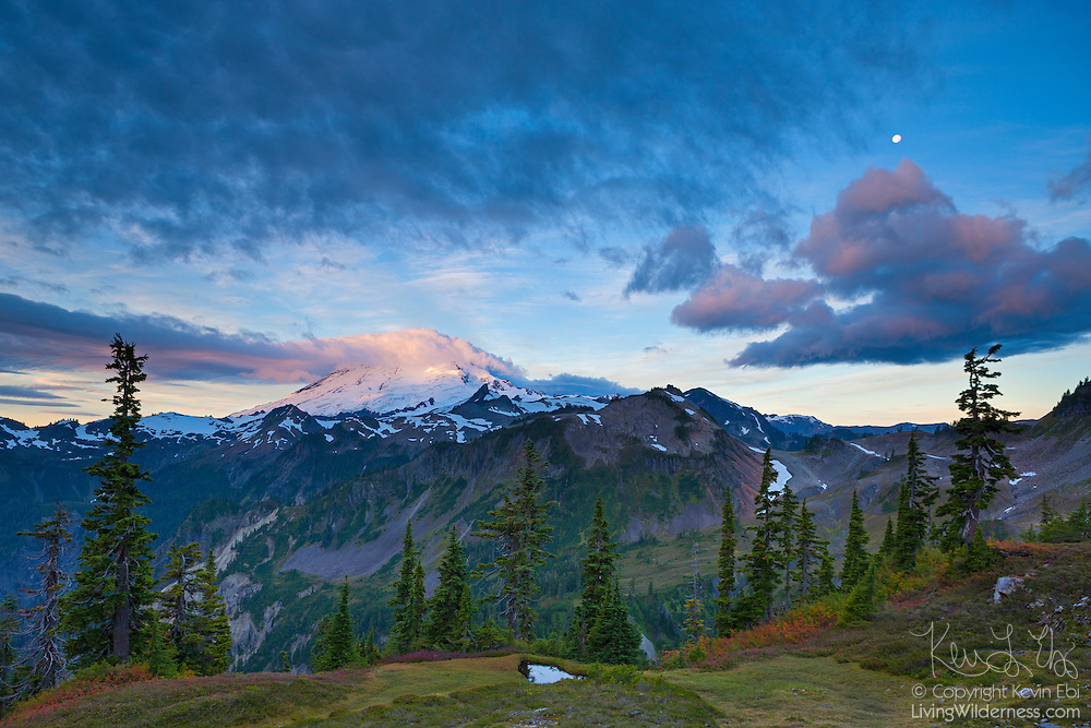 The nearly full moon is visible between layers of storm clouds over Mount Baker, an active volcano in the North Cascades of Washington state. Mount Baker, 10,781 feet (3,286 meters) tall, last erupted in 1880. In this image, its summit is obscured by a cap cloud, a type of cloud that forms when moist air is forced up and over a mountaintop. This scene was captured from an area of the North Cascades known as Artist Point.