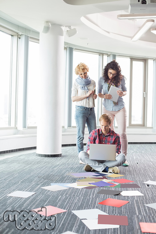 Businesswomen looking at male colleague using laptop on floor in creative office