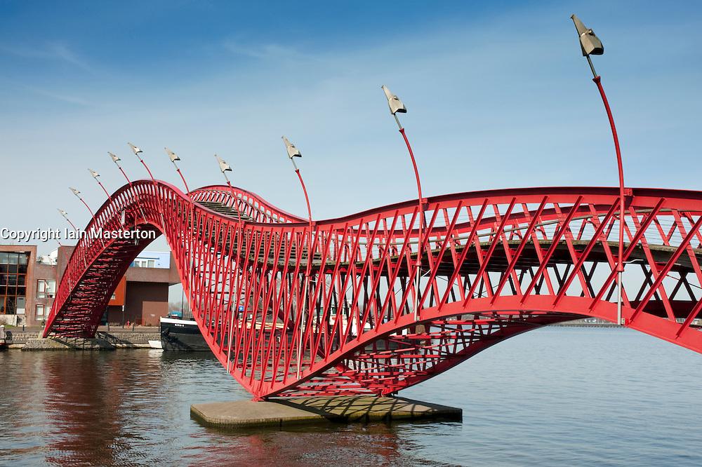 Modern red steel footbridge called Pythonbrug connecting new Borneo and Sporenburg  Island district of Amsterdam Netherlands