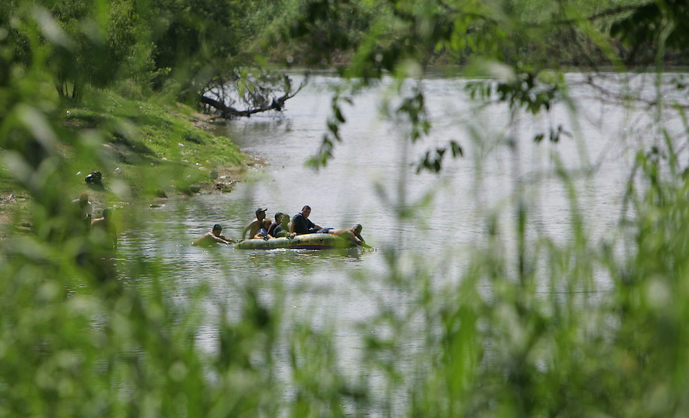 A raft full of illegal immigrants crosses the Rio Grande from a park in Cuidad Miguel Aleman, Tamaulipas to Roma, Texas on June 14.  The immigrants landed at the base of the Roma Bluffs, where the US Border Patrol maintains a watch tower, but no agents were on patrol at the time.
