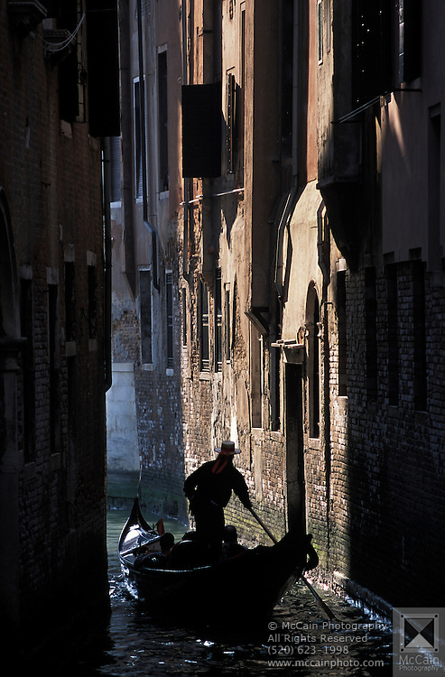 Skillful gondolier steering a gondola through a narrow canal, Venice, Italy..Subject photograph(s) are copyright Edward McCain. All rights are reserved except those specifically granted by Edward McCain in writing prior to publication...McCain Photography.211 S 4th Avenue.Tucson, AZ 85701-2103.(520) 623-1998.mobile: (520) 990-0999.fax: (520) 623-1190.http://www.mccainphoto.com.edward@mccainphoto.com....