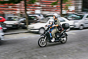 A motor scooter with mother and child ride down a street in Naples, southern Italy.