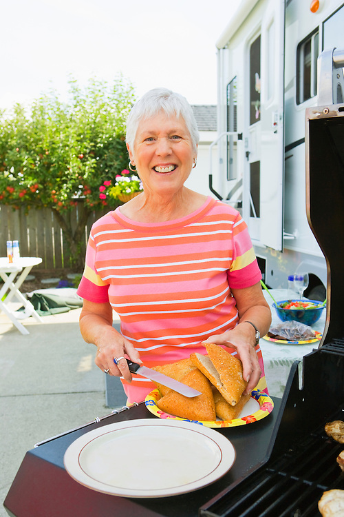 Mature woman portrait standing next to a barbeque with a plate of bread and a knife.