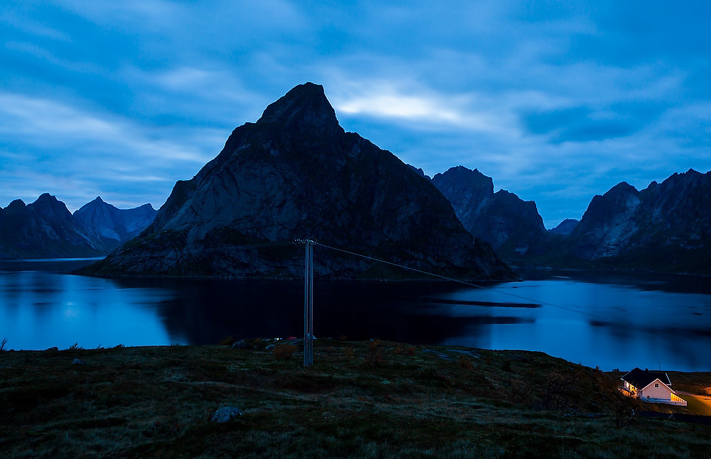A home illuminated at night outside Reine, Moskenesoya, Lofoten Islands, Norway.
