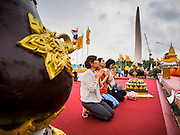 08 JANUARY 2015 - BANGKOK, THAILAND: Women pray and meditate in front of statues of revered Buddhist monks at an altar on Sanam Luang in Bangkok. Buddhist in Bangkok have a chance to meditate in front of seven large statues of revered Buddhist monks and worship a hair relic of the Buddha at a series of altars on Sanam Luang near the Grand Palace in Bangkok.    PHOTO BY JACK KURTZ