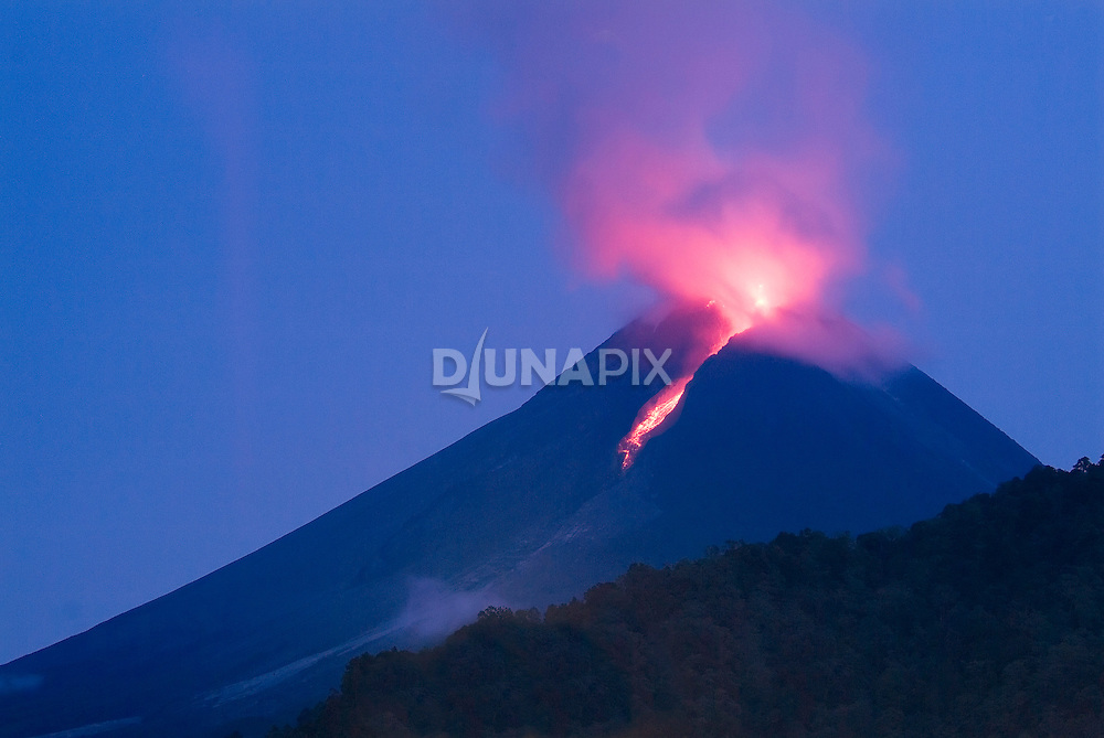 "By pre-dawn light, an ""awan panas"" eruption on Merapi lives up to its name by glowing as a ""hot cloud"". Incandescent lava at the volcano's summit illuminates spewing ash and gas."