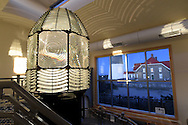 Babylon, NY,  November 7, 2016: --- The Fire Island Lighthouse and Keeper's Quarters are seen through the window of the Lens Building with the original ten foot first order fresnel lens in the foreground.                                            © Audrey C. Tiernan