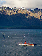 View of the tourist steamship TSS Earnslaw returning to harbor at Queenstown, on Lake Wakatipu; photo taken from alongside the Glenorchy-Queenstown Highway; Otago, New Zealand