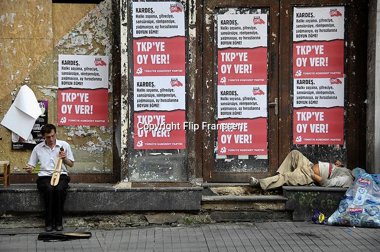 Turkije, Istanbul, 2-6-2011Verkiezingsaffiches van de turkse communistische partij, de TKP, in Istanbul in de aanloop naar de verkiezingen voor het parlement op 16 juni. Een straat muzikant speelt zijn muziek en een zwerver ligt te slapen.Foto: Flip Franssen/Hollandse Hoogte