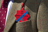 A man wearing an owners and trainers badge outside the paddock.