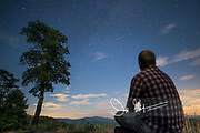 A young man stares up at a star-filled sky along Skyline Drive, Shenandoah National Park, Virginia.