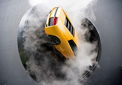 Lamborghini car attached to revolving wall of building during demonstration publicity show with smoke at Autostadt in Wolfsburg Germany
