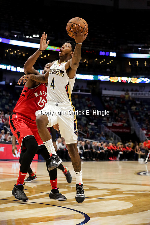 Oct 11, 2018; New Orleans, LA, USA; New Orleans Pelicans guard Elfrid Payton (4) drives past Toronto Raptors center Greg Monroe (15) during the first half at the Smoothie King Center. Mandatory Credit: Derick E. Hingle-USA TODAY Sports