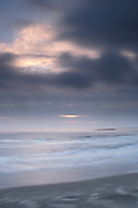 Wind blowing dark clouds at sunet and ocan wave surf breaking on sand Beverely Beach State Park, near Newport, Oregon