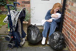 Woman holding a baby sitting on the doorstep surrounded by bags,