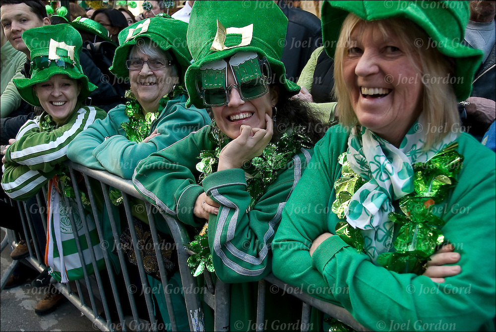 """Crowds watching the New York City's 249th St. Patrick's Parade going up 5th Avenue. Irish for a day when both Irish American and Non Irish American celebrate Irish culture and heritage. People in the crowd wearing green and white hats and wearing buttons """" Kiss Me I'm Irish"""" """"Irish For Tonight"""" and """"Irish"""" have fun as the marchers pass by."""