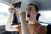 A young man in his twenties inserts a swab into his mouth to reach his tonsils from the rear seat of a car during a self-administered Coronavirus (COVID-19) test in south London. There are four steps to the self-administered Covid-19 test (inserting a swab into the nose and throat) which the public works through in their car, windows up and all communications with army personnel via phone, in a south London leisure centre, on 2nd June 2020, in London, England. The kit provided consists of a booklet, plastic bag, swab, vial, bar codes and a sealable biohazard bag. The swab sample is taken from the back of the throat and nasal passage with the contents sealed and returned to soldiers through a narrow window. The whole process takes between 5-10mins with results available with 48hrs.