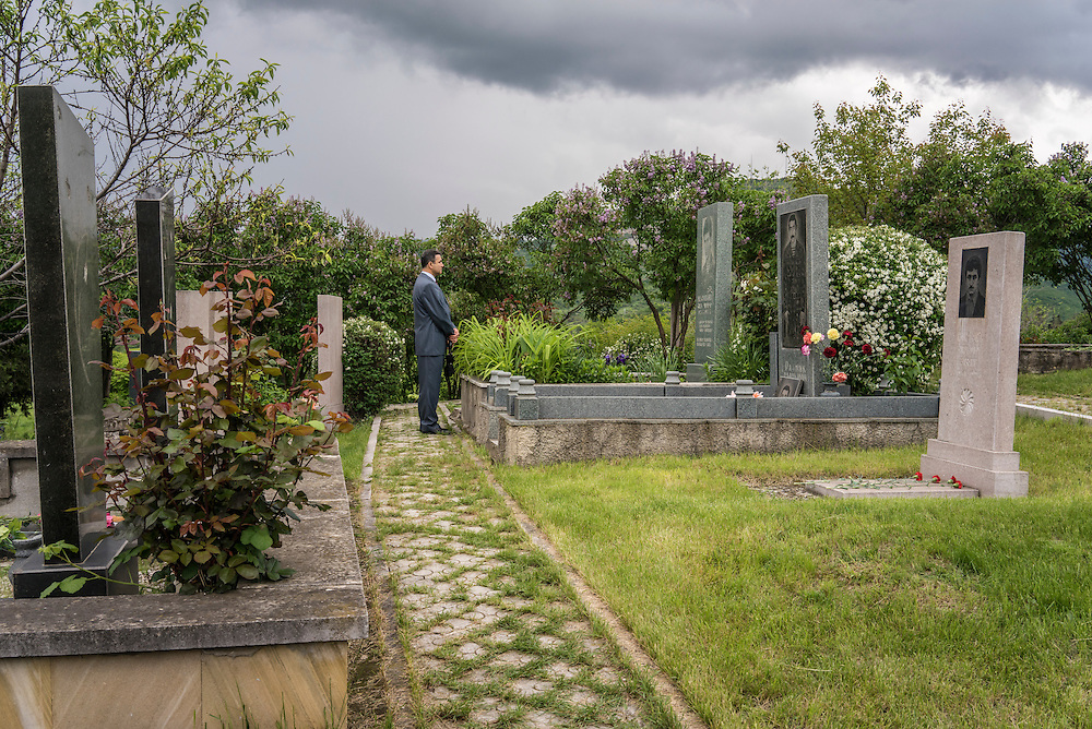 A man pays respects at the grave of a fighter killed in the 1990s war between Armenia and Azerbaijan following a ceremony commemorating both the victory over Nazi Germany in the Second World War as well as the fall of the strategic town of Shushi to Armenian forces on Monday, May 9, 2016 in Stepanakert, Nagorno-Karabakh.