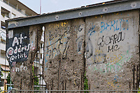 Remnants the Berlin wall , a reminder of the separation of east and west Berlin , now a popular tourist attraction.