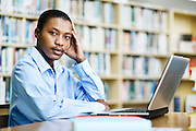 Handsome, serious male student in library looks up from laptop
