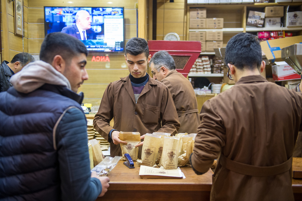 Young adult male prepares bags of coffee for customers at Istanbul Spice bazaar in Turkey