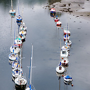 Boats on the River Seiont, as seen from the top of one of the towers at Caernarfon Castle in northwest Wales. A castle originally stood on the site dating back to the late 11th century, but in the late 13th century King Edward I commissioned a new structure that stands to this day. It has distinctive towers and is one of the best preserved of the series of castles Edward I commissioned.