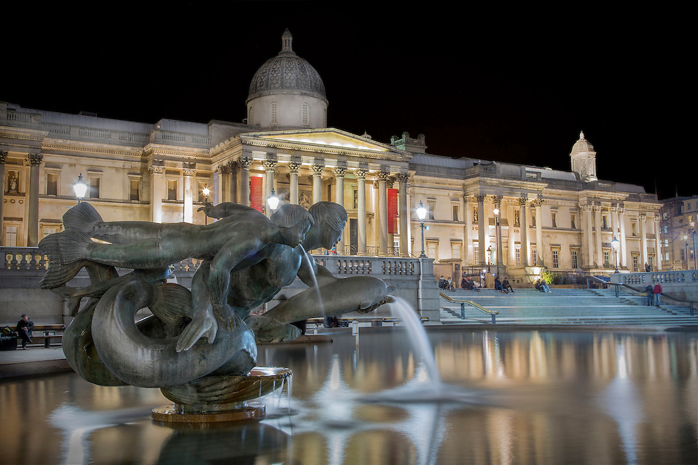 A night shot of a fountain in Trafalgar Square with the National Gallery in the background.<br />