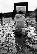 Man sits on bag, in the middle of muddy field watching the football on large screen in the background. Glastonbury 1998