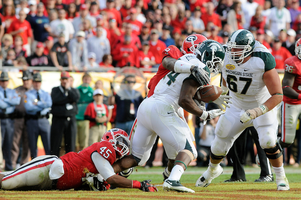 January 2, 2012: Le'Veon Bell of Michigan State is tackled by Christian Robinson and Alec Ogletree of Georgia during the NCAA football game between the Michigan State Spartans and the Georgia Bulldogs at the 2012 Outback Bowl at Raymond James Stadium in Tampa, Florida. The Spartans defeated the Bulldogs 33-30.