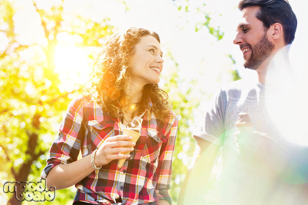 Portrait of young attractive couple walking while eating ice cream with lens flare in background