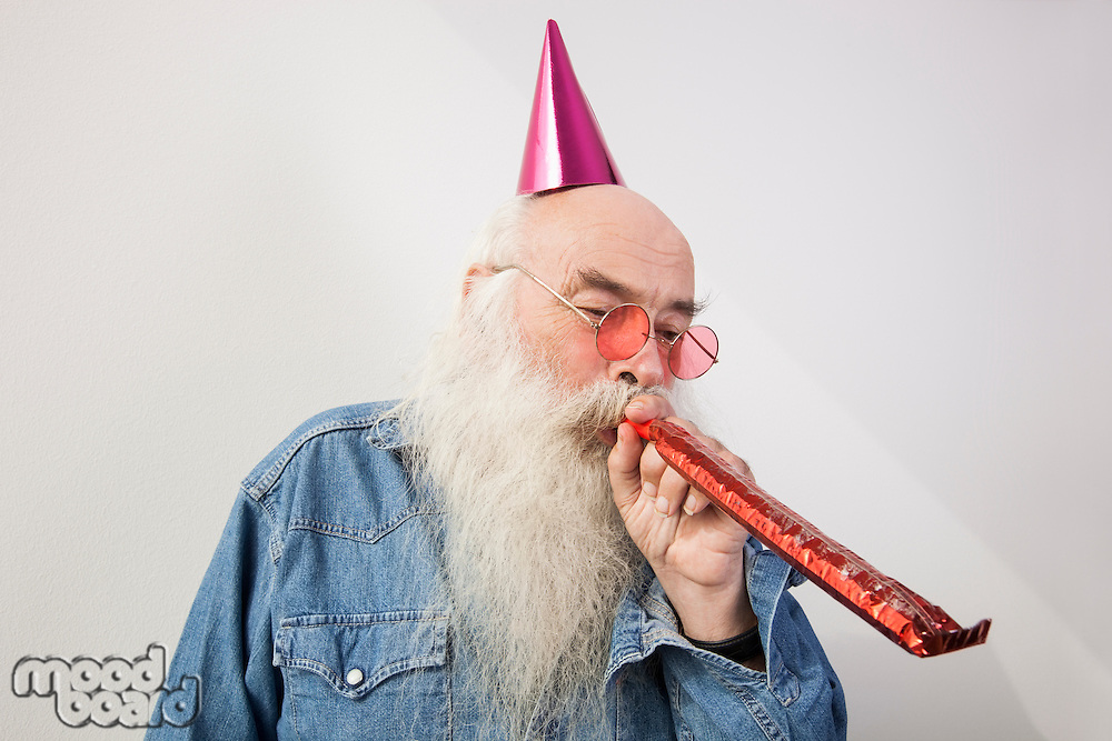 Senior man wearing party hat while blowing horn against gray background