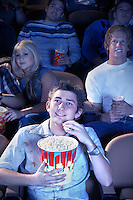 Smiling Man Eating Popcorn watching movie in Theatre