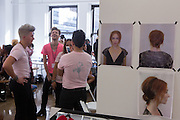 """Hairdressers and makeup artists chat beside a series of """"look"""" photos backstage at the Carmen Marc Valvo Spring 2013 Fashion Week show in New York."""