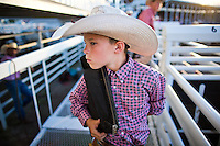 Cooper Stout, 11, of Burwell dons a vest before competing in Junior Steer Riding Friday evening at Nebraska's Big Rodeo in Burwell. (Independent/Matt Dixon)