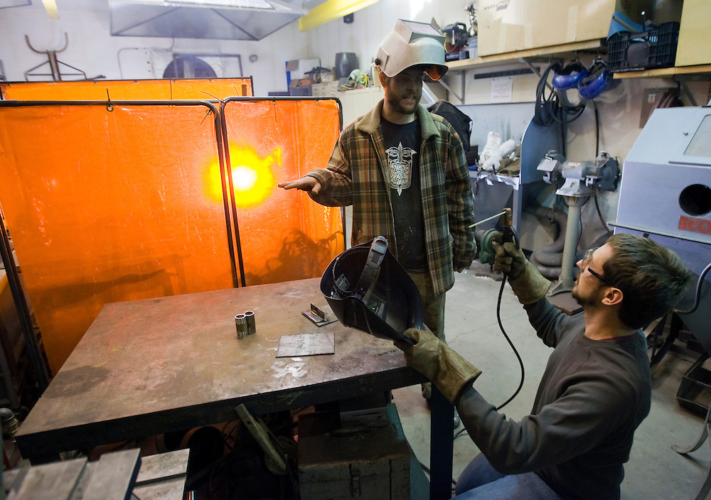 -October 14, Boston, MA-..Instructor and partial owner of the Stonybrook Fine Arts School Benjamin Todd of Mission Hill, MA, left, helps Damon Hyde of Arlington, MA, right, with his shielded metal arc welding technique on Wednesday night as part of a two-month welding course at the school in Jamaica Plain.  An orange dimming barrier protects them from other students welding at another station...(Photo by Brooks Canaday)
