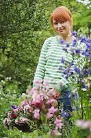 Woman holding basket of flowers in garden portrait