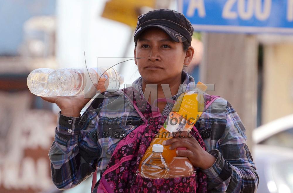 Toluca, México.- Debido a las altas temperaturas que se han registrado, muchos jóvenes aprovechan para vender agua fría como un producto de primera necesidad en las calles  sorteando el peligro entre los vehículos que esperan el cambio de luces en semáforos de la capital. Agencia MVT / José Hernández