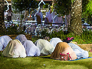 18 JUNE 2015 - PATTANI, PATTANI, THAILAND: Women sit on the grass in front of Pattani Central Mosque during Ramadan services. Thousands of people come to Pattani Central Mosque in Pattani, Thailand, to mark the first night of Ramadan. Ramadan is the ninth month of the Islamic calendar, and is observed by Muslims worldwide as a month of fasting to commemorate the first revelation of the Quran to Muhammad according to Islamic belief. This annual observance is regarded as one of the Five Pillars of Islam. Islam is the second largest religion in Thailand. Pattani, along with Narathiwat and Yala provinces, all on the Malaysian border, have a Muslim majority.     PHOTO BY JACK KURTZ