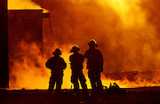 Fire fighters are silhouetted by a building fire.
