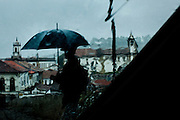 A man, seen through a wet car windshield, shelters himself from the rain beneath an umbrella in Ouro Preto, Brazil.