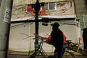 A Japanese man pushes a bicycle loaded with sticks past a corrogated tin house in the fashionable district of Roppongi in Tokyo, Japan