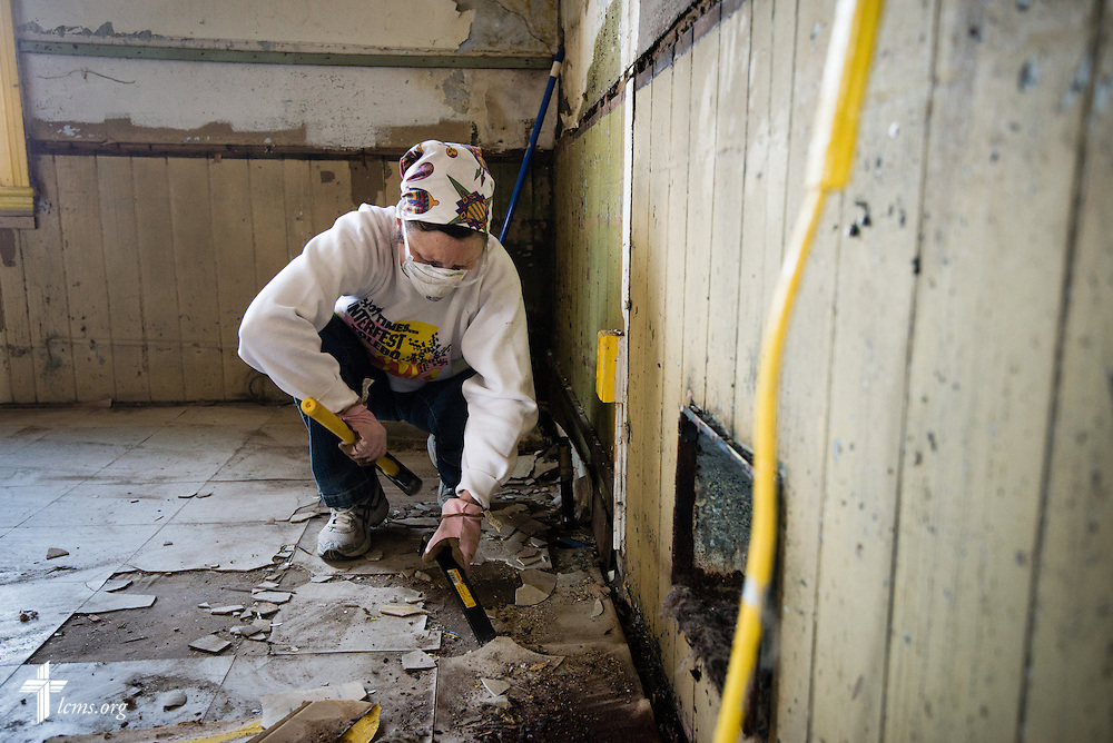 "Elaine Ahrens tears up a floor as she joins other volunteers and members of Emmanuel Lutheran Church as they rehab a vacant and abandoned home adjacent to the church on Saturday, April 12, 2014, in Ft. Wayne, Ind.  The rehab is part of the ""Helping Hand""  initiative from the LCMS National Housing Support Corporation (NHSC) and a coalition of church partners, including Redeemer Lutheran, Emmanuel Lutheran, Zion Lutheran, and St. Peter's Catholic. The initiative is a multi-neighborhood safe housing and repair effort that plans to support nine low-income and/or elderly homeowners. LCMS Communications/Erik M. Lunsford"