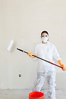 Portrait of a female worker in protective workwear holding a paint roller