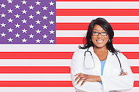 Portrait of confident mixed race female surgeon over American flag